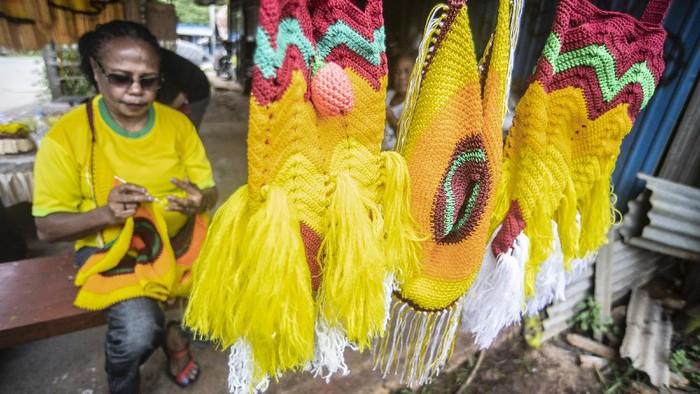 Warga menganyam akar kayu untuk dijadikan noken di Polimak IV Kota Jayapura, Papua, Kamis (26/8/2021). Panitia Besar Pekan Olahraga Nasional (PB PON) Papua akan menyiapkan 25 ribu noken untuk dibagikan kepada atlet, ofisial dan tamu undangan sebagai cinderamata. ANTARA FOTO/Muhammad Adimaja/rwa.
