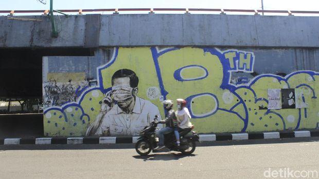 Petugas dari Kecamatan Bandung Wetan masih membersihkan gambar mirip Jokowi dengan mata tertutup masker di Jalan Prabu Dimuntur, Kota Bandung, Kamis (26/8/2021). Terlihat sejumlah petugas masih mengerik kertas sisa gambar tersebut, kemudian memberikan cat putih.