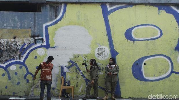 Sejumlah petugas tengah membersihkan sisa mural pria mirip Jokowi di Bandung.