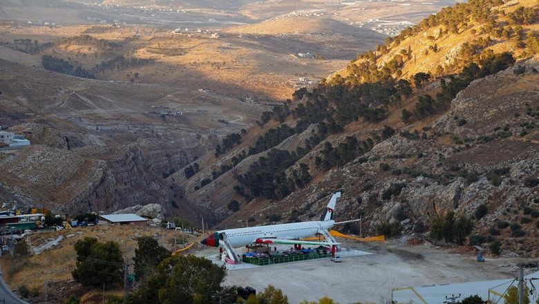 A Boeing 707 aircraft has been converted to a cafe, in Wadi Al-Badhan, just outside the West Bank city of Nablus, Aug. 11, 2021. Few Palestinians in the occupied West Bank get to board an airplane these days. The territory has no civilian airport and those who can afford a plane ticket must catch their flights in neighboring Jordan. But twins brothers, Khamis al-Sairafi and Ata, are offering people the old airplane for customers to board. (AP Photo/Majdi Mohammed)