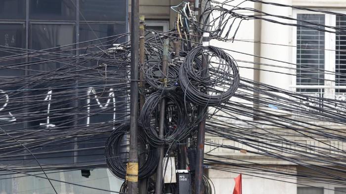 Galian manhole di sepanjang Jl Mampang Prapatan Raya telah selesai digarap. Namun, kabel-kabel yang masih menggantung di tiang belum juga diturunkan.