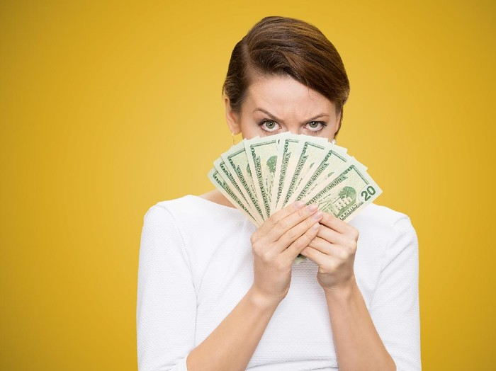 Young grumpy woman covering face with heap of bills looking at camera on yellow background