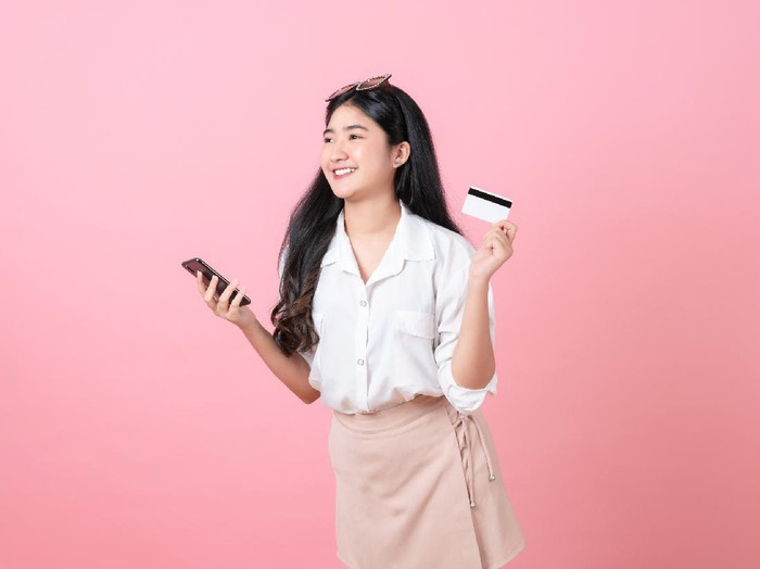 Young smiling Asian woman holding credit card with smartphone and looking to copy space on pink background.