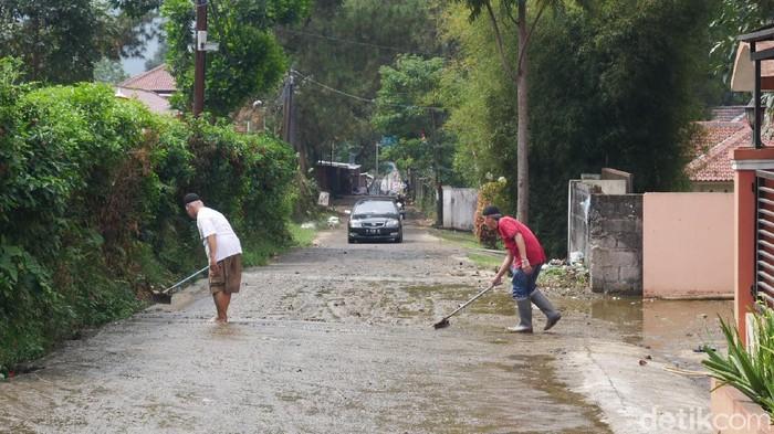 Warga membersihkan kotoran sapi yang meluap hingga mengotori permukiman.