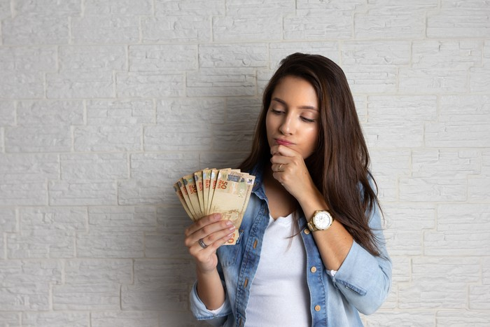 Young pretty woman is looking at cash banknotes, Brazil Currency. Financial, profit, credit, cost, purchase, rich concept.