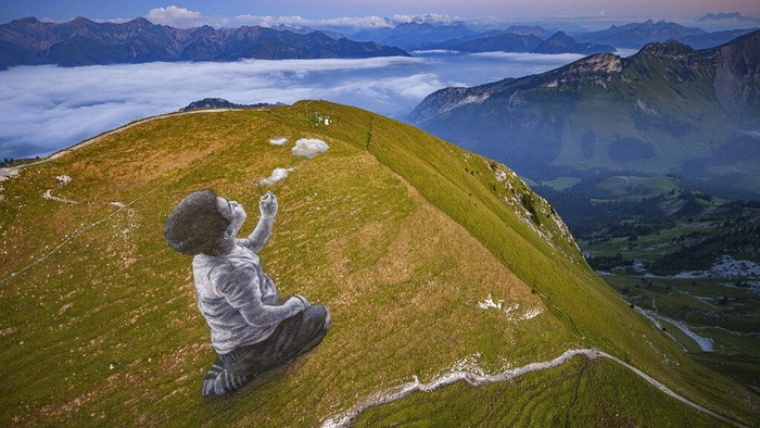 An aerial view shows a giant landart fresco by French-Swiss artist Saype next to the Moleson summit in Moleson-sur-Gruyeres, Switzerland, Wednesday, Aug. 25, 2021. The art piece entitled 'un nouveau souffle' (a new breath) depicts a child blowing clouds towards the horizon. The Fresco covering 1500 square meters was created using biodegradable pigments made out of charcoal, chalk, water and milk proteins. (Valentin Flauraud/Keystone via AP)