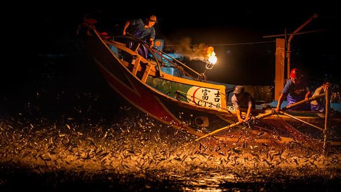 KEELUNG, TAIWAN - AUGUST 20: Fishermen use fire to attract fish on a traditional sulfuric fire fishing