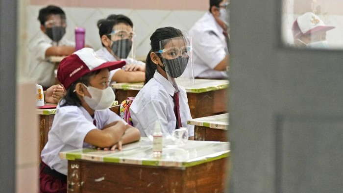 Students wearing face masks to prevent the spread of COVID-19 wash their hands before entering a school building on the first day its reopening in Jakarta, Indonesia, Monday, Aug. 30, 2021. Authorities in Indonesias capital kicked off the school reopening after over a year of remote learning on Monday as the daily count of new COVID-19 cases continues to decline. (AP Photo/Dita Alangkara)