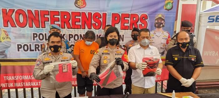 Kapolsek Pondok Aren, Kompol Riza Sativa, memegang barang bukti preman berinisial E, preman ada di belakang berbaju tahanan warna oranye. (Dok Istimewa)