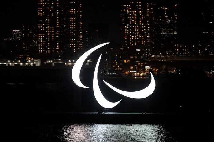 A general view shows the Paralympics symbol rings lit up at night on the Odaiba waterfront in Tokyo on August 21, 2021. (Photo by Charly TRIBALLEAU / AFP)