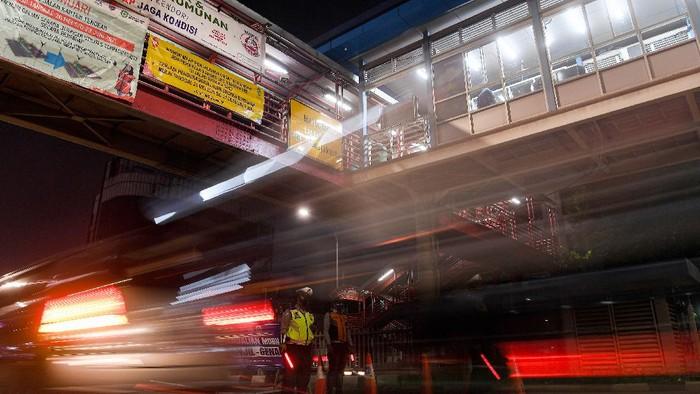 Anggota Polisi dan Dishub mengatur arus lalu-lintas di pos pengendalian mobilitas ganjil-genap kendaraan, Mampang Prapatan, Jakarta Selatan, Senin (30/8/2021). Pemerintah memperpanjang PPKM level 3 dan 4 di Jawa-Bali hingga 6 September 2021. ANTARA FOTO/Sigid Kurniawan/wsj.