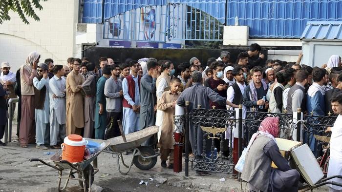 Warga berdatangan untuk melakukan penarikan uang tunai usai bank di Afghanistan kembali beroperasi. Demi ambil uang, warga rela antre berjam-jam.