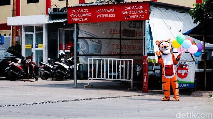 Seorang warga menjadi badut sambil menjual balon di depan SPBU. Dia menjual balon dengan harga seikhlasnya.