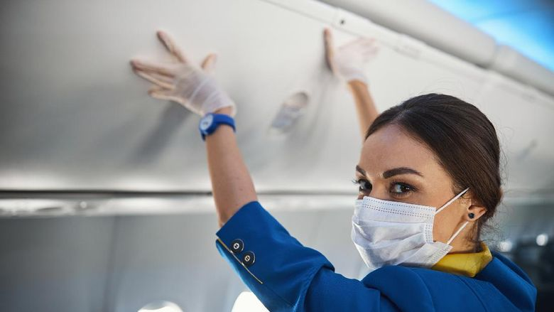 Airline stewardess in protection mask turning her head and looking into camera while pressing hands to overhead bin cover