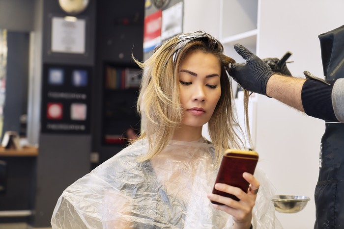 Woman on mobile phone when having hair coloring process in a hair salon