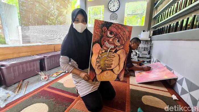 Dila memperlihatkan karya lukisnya.