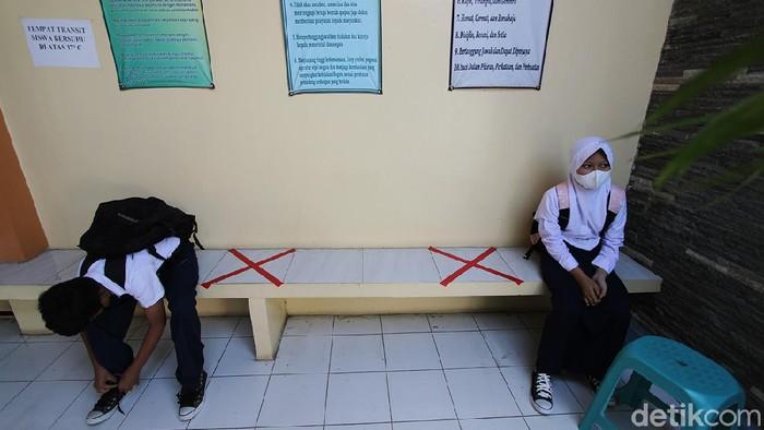 Pelajar SLTPN 22 Solo melaksanakan pembelajaran tatap muka dengan guru di ruang sekolah, Solo, Jawa Tengah, Kamis (2/9). Sekolah tersebut menerapkan aturan kehadiran 50 persen pelajar dan membatasi waktu tatap muka dari pukul 07.30 hingga 09.00 WIB dengan pemberlakuan protokol kesehatan ketat.