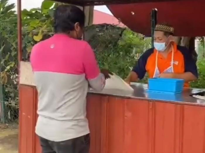 kurir makanan bantu penjual roti canai yang sedang sibuk siapkan pesanan