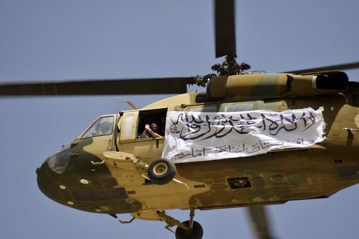 A helicopter displaying a Taliban flag flies above Taliban supporters gathered to celebrate the US withdrawal of all its troops out of Afghanistan, in Kandahar on September 1, 2021 following the Talibans military takeover of the country. (Photo by JAVED TANVEER / AFP)