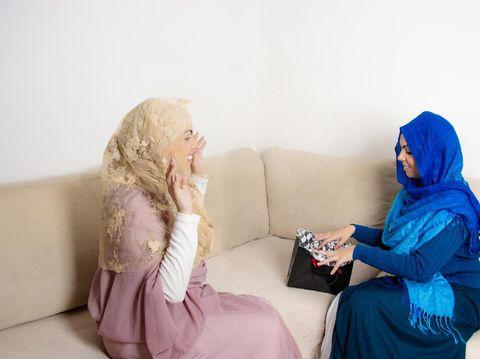 Two young Muslim women 30 years sitting on the sofa opening shopping carton, gift