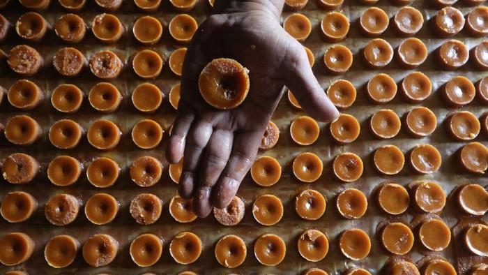 Perajin mencetak gula merah berukuran kecil di Desa Nambaan, Kediri, Jawa Timur, Jumat (3/9/2021). Perajin gula merah di tempat tersebut melakukan inovasi dengan memperkecil ukuran gula merah dari sebelumnya seberat 500 gram per buah menjadi ukuran kecil seberat 35 gram per buah agar lebih mudah diterima pasar seiring menurunnya permintaan saat pandemi COVID-19. ANTARA FOTO/Prasetia Fauzani/aww.