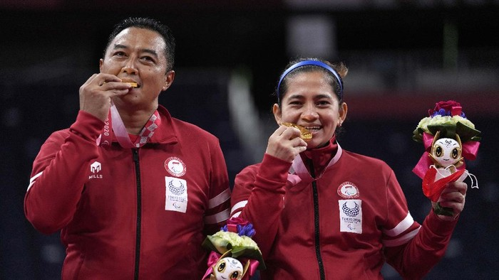 Indonesia's Hary Susanto, left, and Leani Ratri Oktila salute to the flag during the national anthem after receiving a gold medal for mixed doubles SL3-SU5 gold medal match at the Tokyo 2020 Paralympic Games, Sunday, Sept. 5, 2021, in Tokyo, Japan. (AP Photo/Kiichiro Sato)