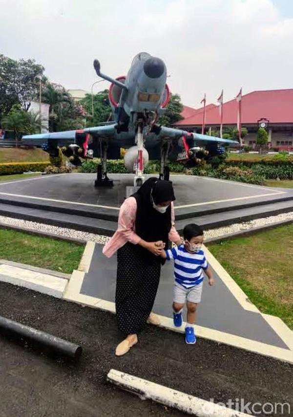 Seorang anak berjalan di depan sebuah pesawat yang terpajang di depan halaman Museum Satriamandala, Jl Gatot Subroto, Jakarta.