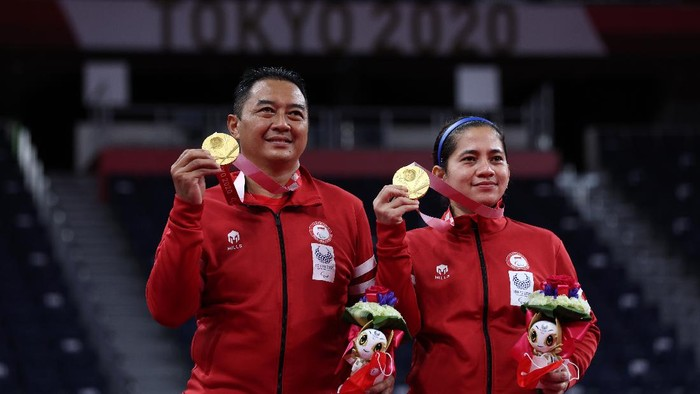 TOKYO, JAPAN - SEPTEMBER 05: Gold medalist Susanto Hary and Oktila Leani Ratri of Team Indonesia pose on the podium at the medal ceremony for the Mixed Doubles SL3-SU5 on day 12 of the Tokyo 2020 Paralympic Games at Yoyogi National Gymnasium on September 05, 2021 in Tokyo, Japan. (Photo by Kiyoshi Ota/Getty Images)