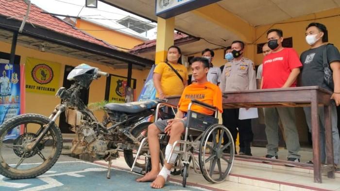 Pelaku, Anton (AN), duduk di kursi roda dengan kaki diperban.