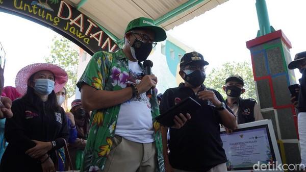 Menparekraf sandiaga Uno saat meneken prasasti Pulau Untung Jawa sebagai salah satu dari 50 besar desa wisata ADWI 2021.(Femi Diah/detikcom)