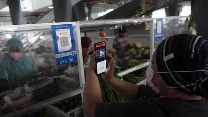 Warga melakukan transaksi menggunakan metode bayar scan QRIS dengan aplikasi DOKU e-Wallet di Pasar Tradisional Prawirotaman, Yogyakarta, Minggu (5/9/2021). Saat ini pemerintah Yogyakarta menggencarkan transaksi non tunai di pasar tradisional seperti di Pasar Prawirotaman maupun Pasar Beringharjo. ANTARA FOTO/Andreas Fitri Atmoko/aww.