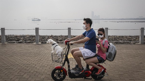 Pengunjung menaiki sepeda listrik usai berolahraga di kawasan Pantai Maju, Jakarta Utara, Minggu (5/9/2021).