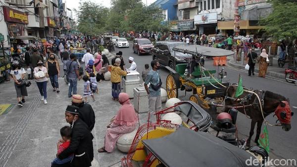 Wisatawan ada yang berbelanja oleh-oleh, ada pula yang duduk-duduk sembari makan menikmati minggu sore di kawasan Jalan Malioboro.