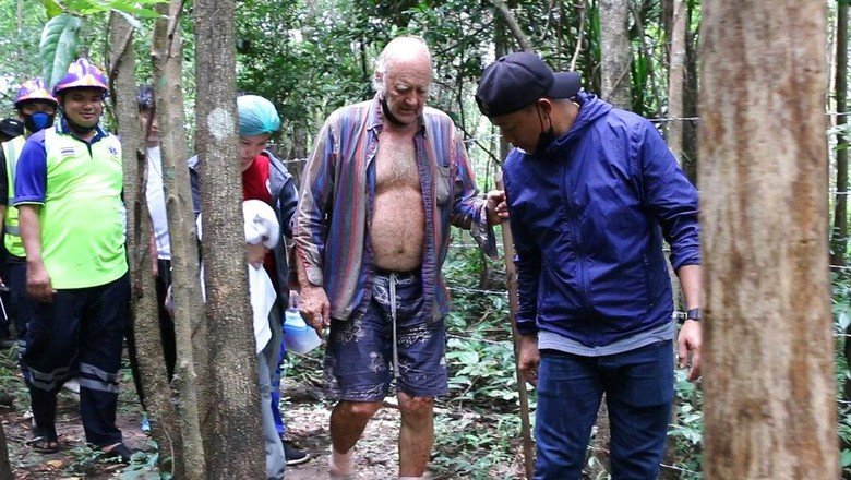 Rescuers lead Barry Leonard Weller, 72, out of the jungle, in Thailands northeastern Khon Kaen province, Friday, Sept. 3, 2021. A 72-year-old British man has been found safe three days after disappearing in a thick jungle in northeastern Thailand while going to visit friends on a motorbike. A member of a local volunteer team that helped rescue him said a hunter came across Barry Leonard Weller in a remote forest in Khon Kaen province. He was asleep on a rock formation after climbing it to try to see a route out. (AP Photo/Tanadon Sribura )