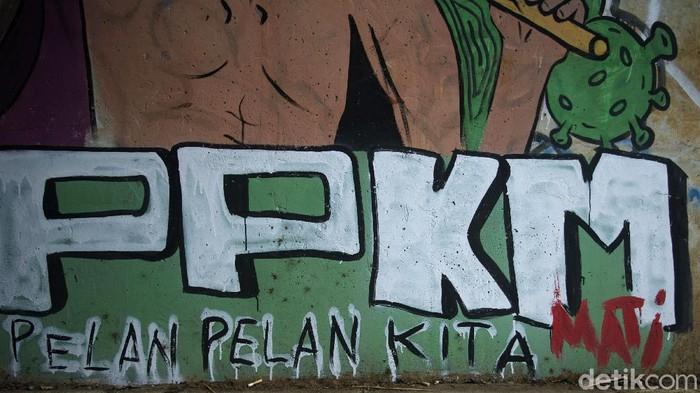 Pengendara motor melintas di kawasan Kabupaten Bogor, Jawa Barat, Senin (6/9/2021). Nampak sebuah mural Pelan Pelan Kita Mati (PPKM) terlihat di sebuah underpass. Sebelumnya mural terkait covid dan sindiran ke pemerintah berjamuran, satu per satu mural yang dibuat dihapus petugas.