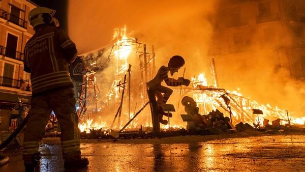Seorang petugas pemadam kebakaran mengendalikan api yang berkobar selama digelarnya festival Las Fallas di Valencia, Spanyol, pada Minggu (5/9/2021), waktu setempat.