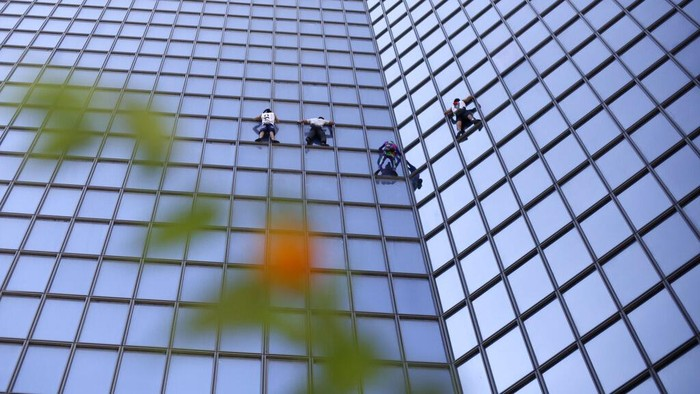 French climber Alain Robert, second right, known as Spiderman, and climbers Marcin Banot, from Poland, France's Alexis Landot and Leo Urban, climb the 187-meters (613-foot) TotalEnergies tower in La Defense business district outside Paris, Tuesday, Sept.7, 2021. (AP Photo/Rafael Yaghobzadeh)