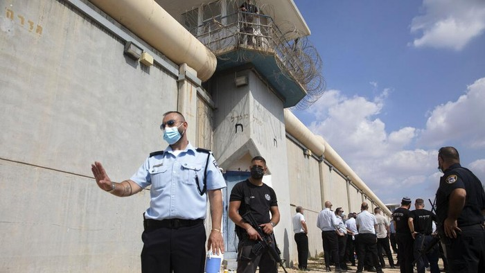 Police officers and prison guards inspect the scene of a prison escape outside the Gilboa prison in Northern Israel, Monday, Sept. 6, 2021. Israeli forces on Monday launched a massive manhunt in northern Israel and the occupied West Bank after six Palestinian prisoners escaped overnight from a high-security facility in an extremely rare breakout. (AP Photo/Sebastian Scheiner)