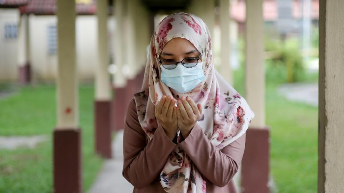 A female adult is putting both hands together for doa (Muslim way of praying) during partial lockdown in Malaysia.