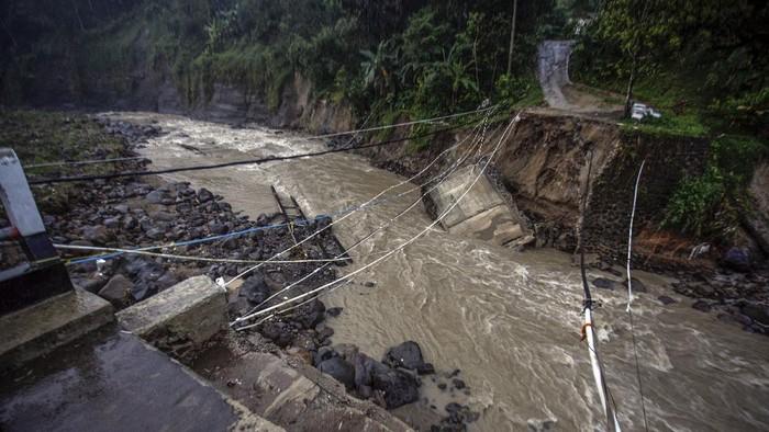 Warga melihat kondisi jembatan perbatasan Kecamatan Sukajaya dan Kecamatan Nanggung yang terputus di Desa Urug, Sukajaya, Kabupaten Bogor, Jawa Barat, Selasa (7/9/2021). Ambruknya jembatan yang disebabkan banjir bandang aliran Sungai Cidurian itu mengakibatkan akses jalan warga antar Kecamatan terputus. ANTARA FOTO/Yulius Satria Wijaya/rwa.