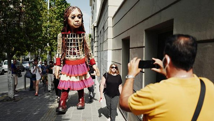 PIRAEUS, GREECE - SEPTEMBER 04: Artists perform alongside Little Amal, a giant puppet depicting a young Syrian refugee girl, outside the Municipal Theatre of Piraeus on September 4, 2021 in Piraeus, Greece. Little Amal is a 3.5 metre puppet walking 8,000 kilometres across Europe to highlight the plight of child refugees. There are some 26 million refugees worldwide, and more than half of them are children. (Photo by Ayman Oghanna/Getty Images)
