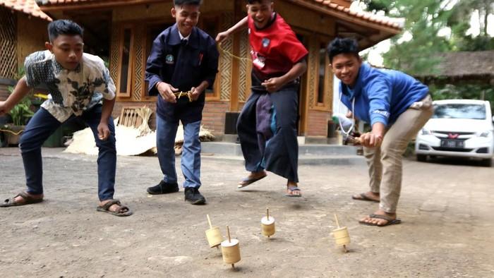 Anak-anak bermain gasing di Kampoeng Baca Taman Rimba (Batara) Papring, Kalipuro, Banyuwangi, Jawa Timur, Selasa (7/9/2021). Permainan tradisional gasing yang terbuat dari bambu itu masih dilestarikan oleh Kampoeng Batara sebagai sarana edukasi agar tidak kecanduan gawai. ANTARA FOTO/Budi Candra Setya/rwa.