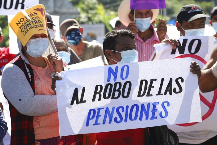 A man holds a sign with a message that reads in Spanish;