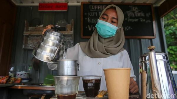 Seorang pelayan tengah membuat kopi.
