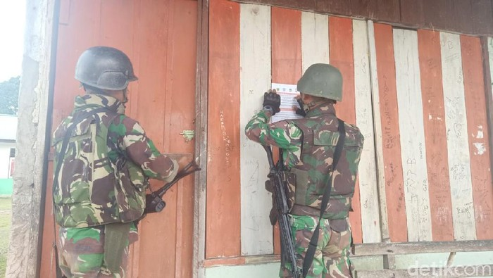 Sejumlah personel TNI berpatroli dan menempelkan selebaran ajakan kepada warga untuk kembali ke kampung. (dok Kodam Kasuari)