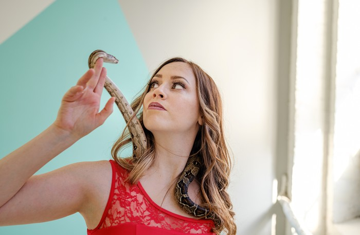 Portrait of Female acrobat with pet snake during the practice in the studio.