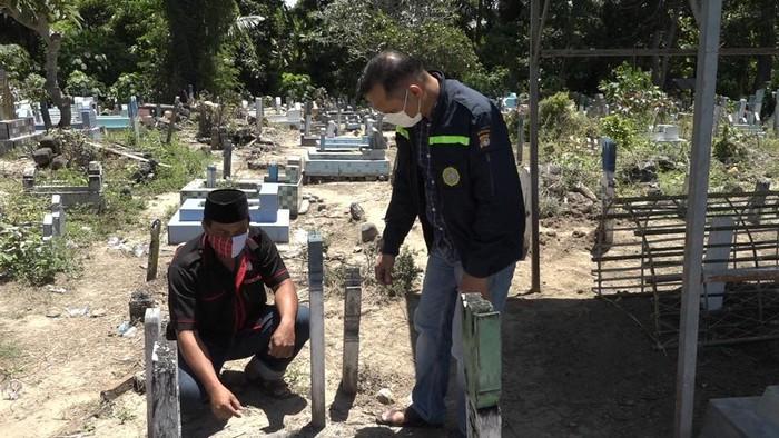 Warga saat menunjukkan lokasi penemuan botol isi foto wanita di kuburan (Abdy-detikcom)