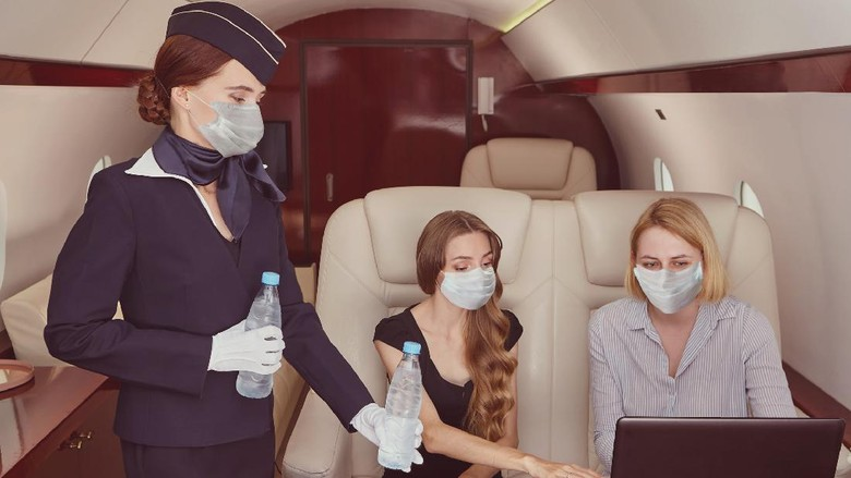 Air hostess in medical protective mask from coronavirus covid-19 pandemic inside airplane is serving passengers in the first class.
