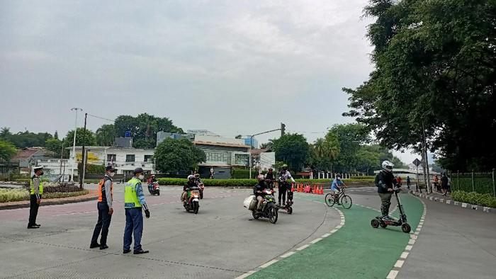 Petugas mengalihkan pesepeda ke Jl Hang Lekir, Minggu (12/9/2021).