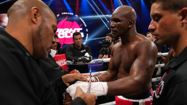Former heavyweight champion Evander Holyfield, center, has his gloves and hand wraps removed after losing in the first round of a boxing match against former MMA star Vitor Belfort, Saturday, Sept. 11, 2021, in Hollywood, Fla. (AP Photo/Rebecca Blackwell)